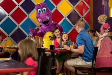 Dutch Wonderland mascot Duke the Dragon entertains family eating a meal