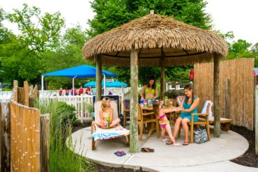 Family sits under a shaded cabana at water play area