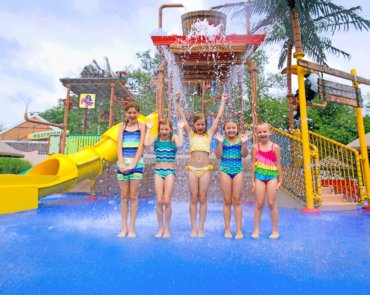 Five young girls standing in front of a spilling bucket water play structure