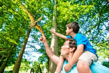 Father and son pointing to a model flying dinosaur in the trees