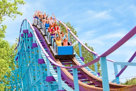 Families riding a blue and purple wooden roller coaster