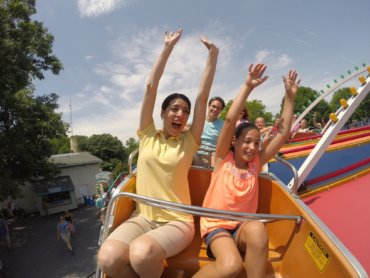 Woman and girl riding Twister ride with their hands in the air