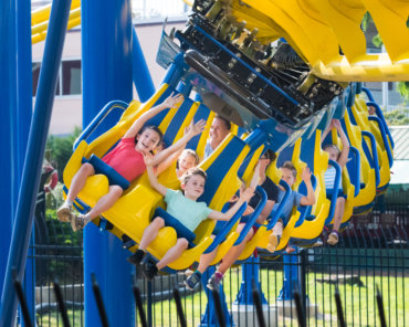 Children riding yellow and blue suspended roller coaster